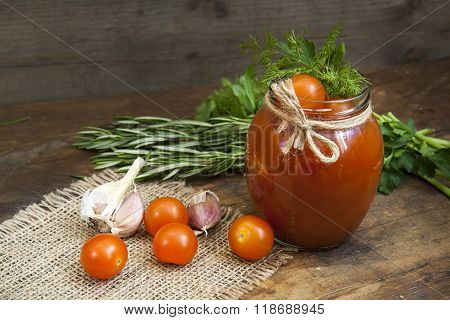 Canned marinated tomatoes in tomato juice on a wooden table