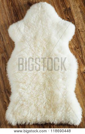sheepskin carpet on wooden background