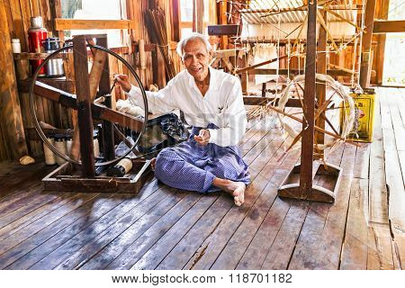INLE LAKE, MYANMAR - November 22, 2015: Weaving in an old fashioned way in a factory for clothing at Inle Lake in Myanmar