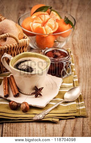 Coffee and fruits for breakfast. Tangerines and sweet jam on wooden board in rustic style