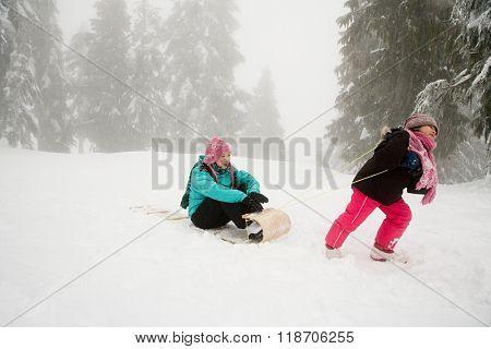 Girl pulling mother on toboggan