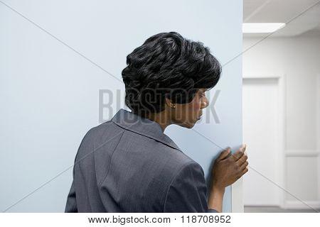 Woman hiding peering round corner