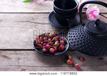 Dry Rose  Tea In Bowl And Traditional Asian Tea Set  On Aged Wooden Background.
