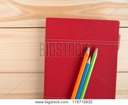 Colorful Pencils Put On Red Diary Book On The Wooden Desk