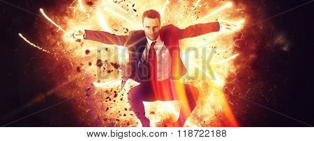 Wide view of leaping businessman in suit and tie surrounded by fiery explosion and flying sparks