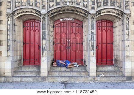 Man Sleeps In Front Of Church Door On 7Th Ave In New York City