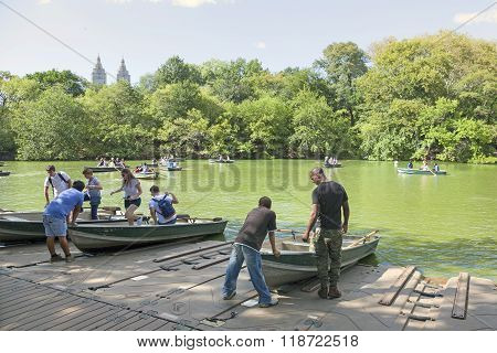 People Row In Boats On New York City Central Park Pond Near Boathouse