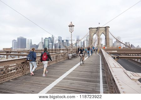 People Engaged In Bike Run And Others Walking On Brooklyn Bridge New York