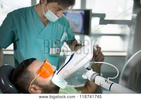 Man having teeth whitening by dental UV whitening device,dental assistant taking care of patient