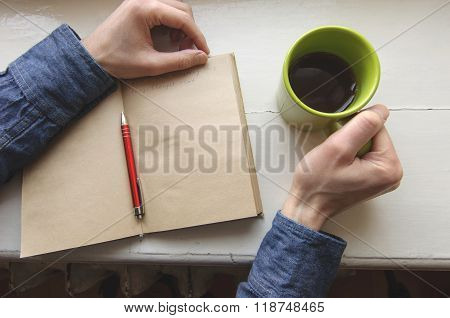 Male right hand holding cup with writing on notebook