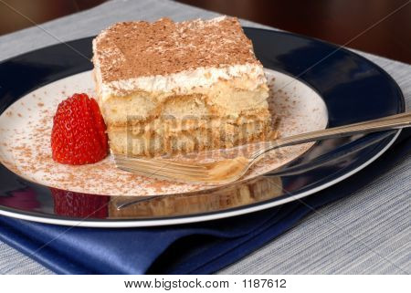 Side View Of A Piece Of Tiramisu Dusted With Cocoa With A Fork O