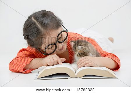 Little Asian girl reading a book with lovely Persian kitten
