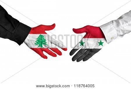 Lebanon and Syria leaders shaking hands on a deal agreement
