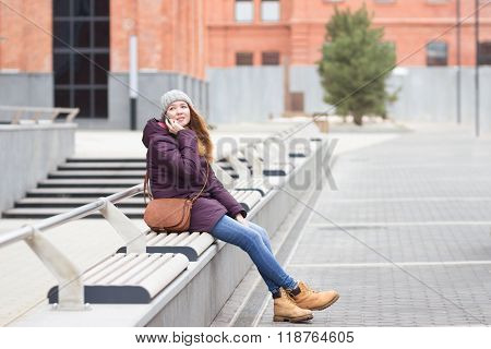 Young Woman Using A Smartphone While Sitting Outdoors On A Bench