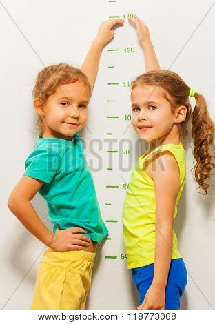 Two girls smile show height on wall scale at home