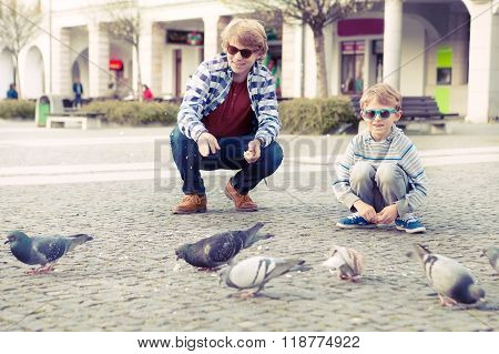 Two Brothers Feeding The Doves On The Old European City Square