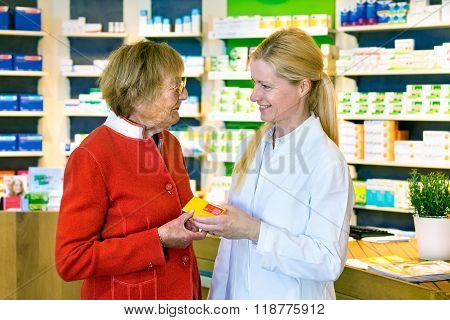 Friendly Pharmacist Giving Customer Prescription