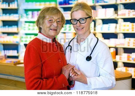 Happy Doctor With Female Patient In Pharmacy