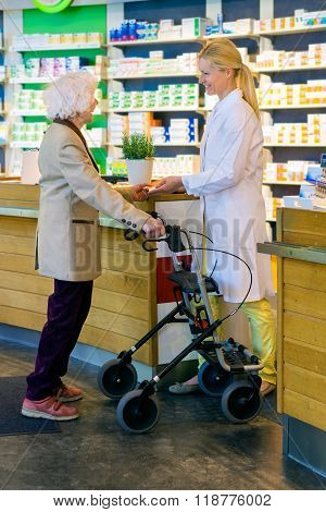 Elderly Customer Using Walker With Pharmacist