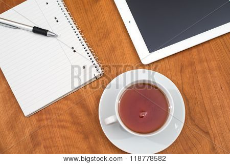 Tablet Pc And Notepad And A Cup Of Tea On Wooden Table From Above