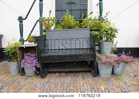 Traditional Dutch Wooden Bench Surrounded By Decorative Plants On The City Street