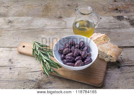 Kalamata Black Olives, Oil, Bread And Rosemary Garnish On Rustic Wood