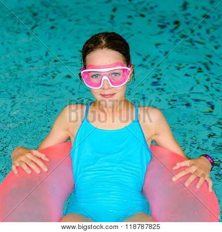 Happy Girl In Pink Goggles Mask In The Swimming Pool