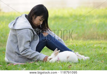 Child And Her Pet Bunny Playing Outdoors