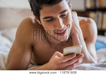 Handsome young man in bed typing on cell phone