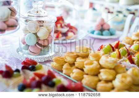 Table setting. Colorful macarons and cakes.