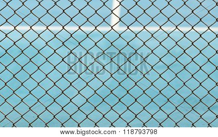 Metal Mesh Fence On Blurred Background Of Blue Tennis Hard Court