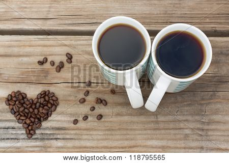 Black Coffee For Two Next To Heart Shaped Coffee Beans