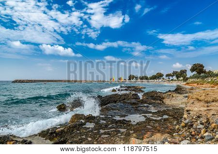 Beautiful Cretan rocky coastline with blue sea and surfers at the background
