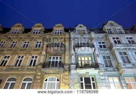 Facades of tenement houses with balconies during the night