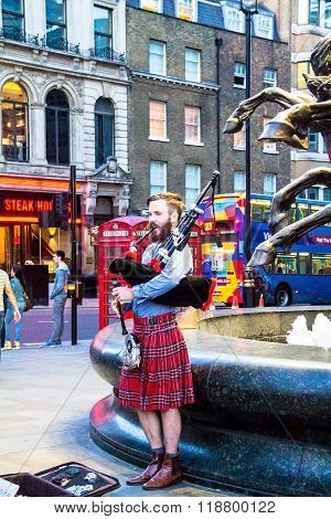 Unidentified Young Man With A Bagpipe In The Scottish National Dress At Piccadilly Circus