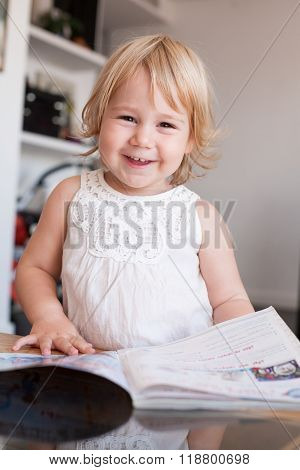 Smiling Baby Thumbing Magazine