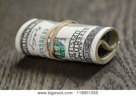 roll of new style hundred dollar bills on table