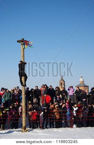 Suzdal, Russia - February 21, 2015: Shrovetide In Russia. Man Climbing The Pole For Prize During Win