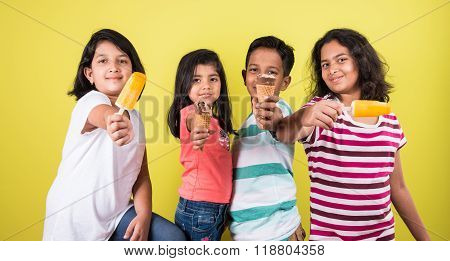four cute little indian kids eating ice cream, asian girls and boy and ice cream, isolated on green