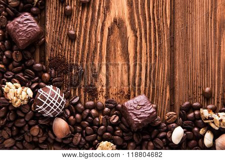 Roasted coffee beans, chocolate, candy, nuts  and the place for inscriptions on wooden background