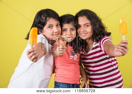 three cute little girls eating ice cream, asian girls and ice cream, isolated on green background