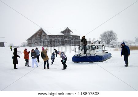 Karelia, Kizhi, Russia - January, 2016: Tourists Photographed Against The Backdrop Of A Hovercraft
