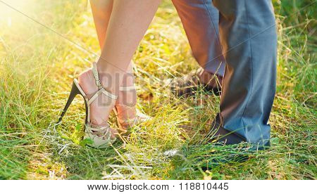 lower legs of woman and man standing opposite each other