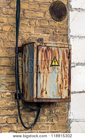 Aged electric switch box in front of old brick wall background