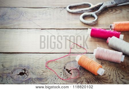 Scissors, bobbins with thread and needles. Old sewing tools on the old wooden background. Vintage Ba