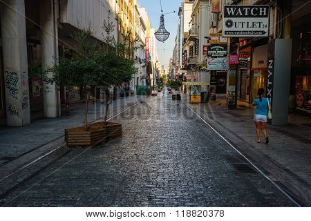 ATHENS, GREECE - AUGUST 15, 2015: Empty morning street of Athens town with lonely woman walking ahead.