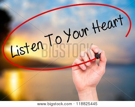 Man Hand Writing Listen To Your Heart With Black Marker On Visual Screen