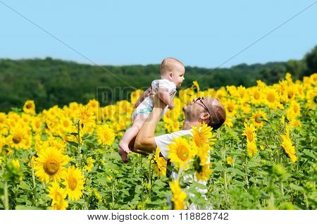 Father With Son On The Sunflower Field