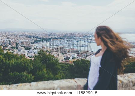 Woman looking down at the City of Palma in Majorca. Back view of young woman standing on viewpoint above city port. girl is blurred and city is in focus