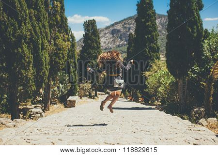 happy fashion young woman jumping on Calvary stairway